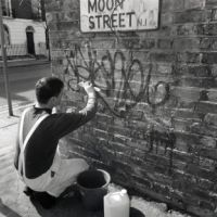 LB Islington, a building services officer cleans graffiti from a property on Moon Street, 1993